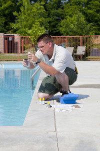 A Temecula pool cleaning service tech checking the chemical levels in a pool